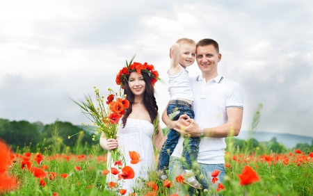 Beautiful young family walking on the poppy field in summer  photo