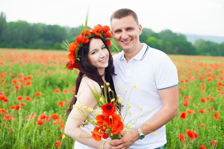 Beautiful young family walking on the poppy field in summer  Stock Photo - 16333477