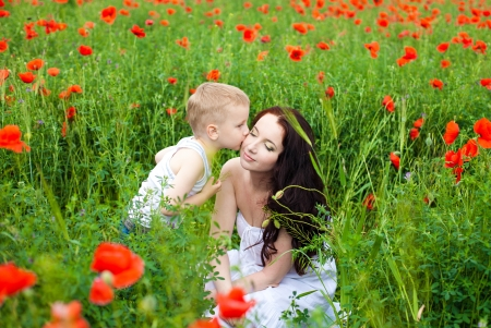 Beautiful young family mother and her son walking on the poppy field in summer  Stock Photo