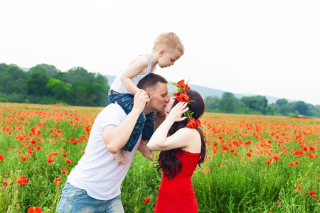 Beautiful young family walking on the poppy field in summer Stock Photo - 16333594