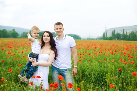 Beautiful young family walking on the poppy field in summer Stock Photo - 16345427
