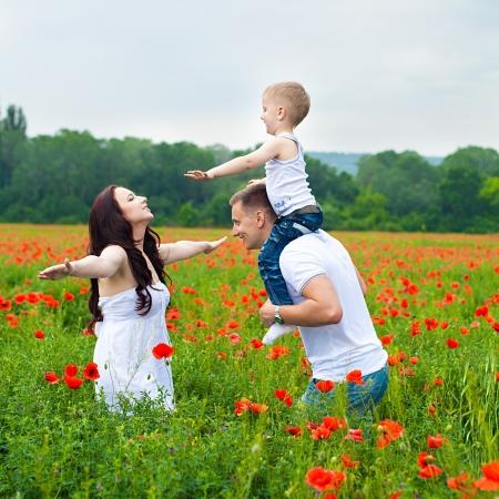 Joven y bella familia caminando en el campo de amapolas en verano