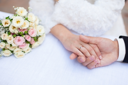 Groom and bride holding hands with wedding rings and bouquet photo