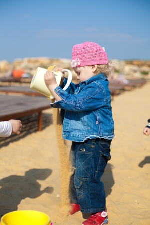 Small child playing in the sand with shovels and buckets on the shore of the sea Stock Photo - 16347564