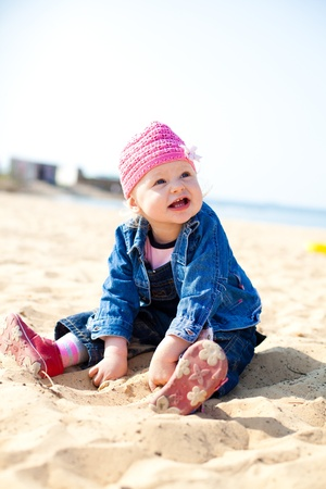 Small child playing in the sand with shovels and buckets on the shore of the sea Stock Photo - 16345432