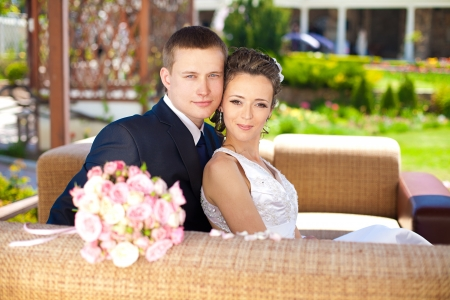 The bride and groom on their wedding day, sitting at a table with the bridal bouquet  photo