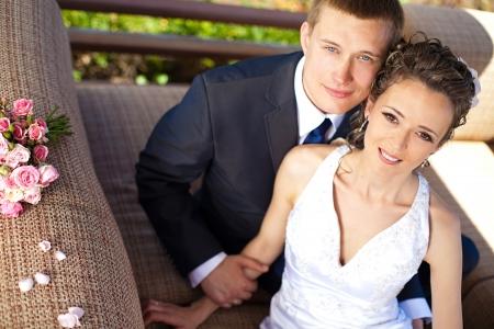 La mari�e et le mari� le jour de leur mariage, assis � une table avec le bouquet de la mari�e photo