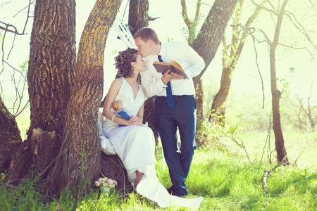 Groom is reading a book of his beloved bride  Posing against a tree in a park in your wedding day in the summer