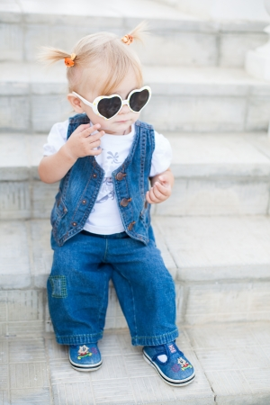 Cute little blond girl posing in sunglasses on the steps  Summer  photo