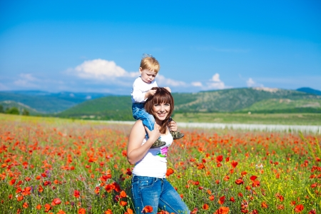 Happy young mother with a child in a poppy field photo