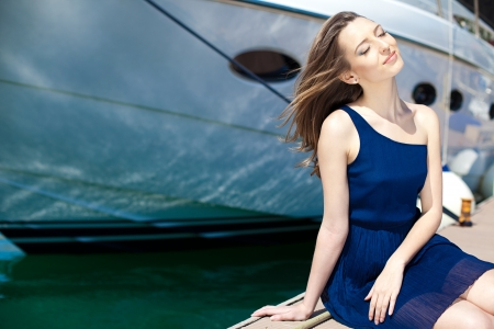 Young beautiful brunette woman relaxing on the dock near the boat on a sunny day in spring  photo
