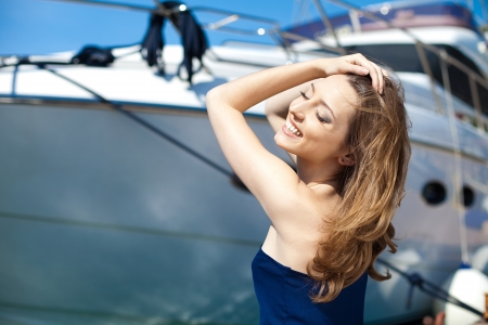 Young beautiful brunette woman relaxing on the dock near the boat on a sunny day in spring