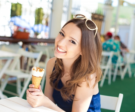 Beautiful young woman relaxing in a bar in the open air, with ice cream  A sunny day in summer photo