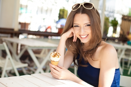 Beautiful young woman relaxing in a bar in the open air, with ice cream  A sunny day in summer