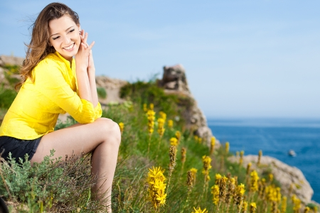 Beautiful brunette woman resting on a mountain near the sea  In summer, sunny day  Stock Photo - 16349315