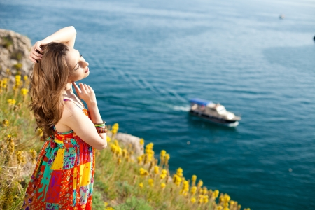 Beautiful brunette woman resting on a mountain near the sea  In summer, sunny day  Stock Photo
