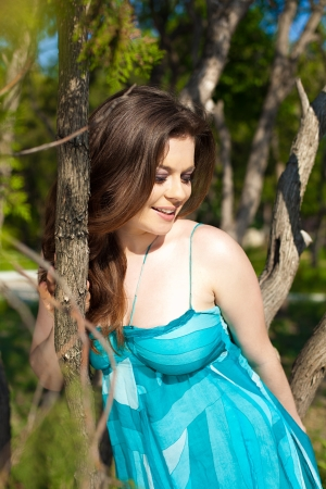 appealing attractive: Young beautiful brunette in blue dress posing in a park on a green meadow in spring sunny day  Stock Photo