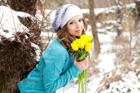 Portrait of a beautiful young girl with a bouquet of yellow tulips in the park  photo