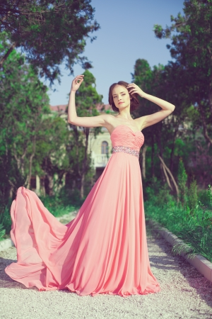 Beautiful young woman in a bright dress posing outdoors in the spring against the backdrop of the park  photo