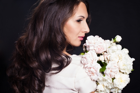 Portrait beautiful brunette woman poses with bouquet of white flowers  Fashion photo in studio  photo