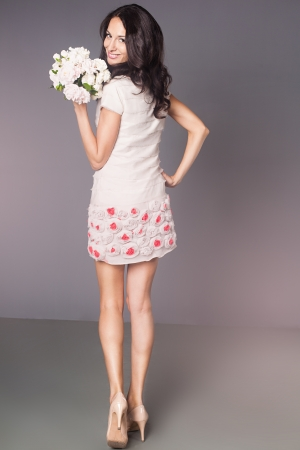 Beautiful brunette woman poses with bouquet of white flowers  Fashion photo in studio  photo