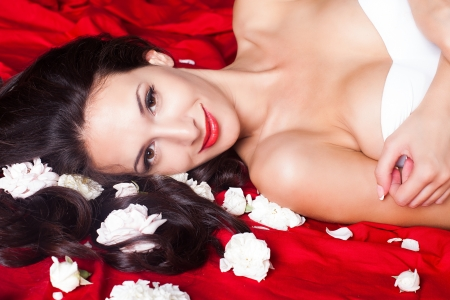 Beautiful brunette girl, a portrait in the studio on a red background with leaves of roses  photo