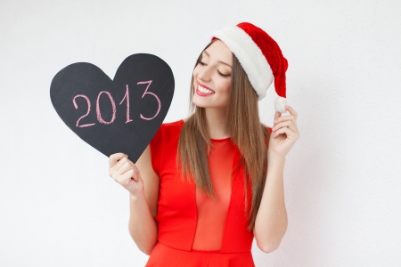 Beautiful young woman in a red Christmas hat and red dress, holding a sign in the form of a heart and the words  2013  over white wall background  A series of photos in my portfolio Stock Photo - 16406483