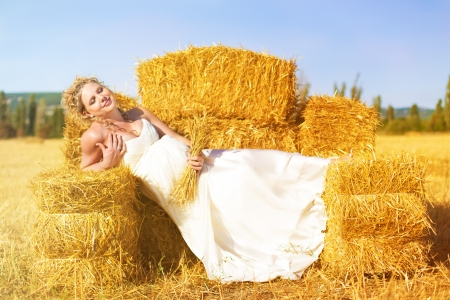 haymow: Beautiful pregnant blonde posing in a yellow field near the haystacks  Summer