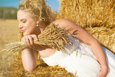 Beautiful pregnant blonde posing in a yellow field near the haystacks  Summer  photo