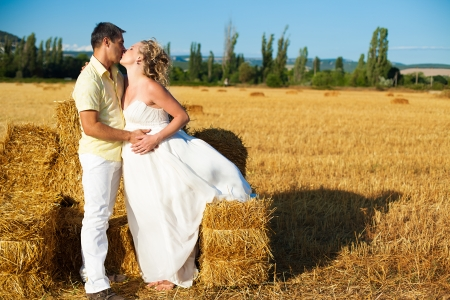 Beautiful couple pregnant wife and husband enjoyed the stay on a yellow field on a background of blue sky and hay  Summer  photo