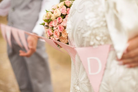 Happy pregnant bride and groom holding a garland with flags with the words  Just married  pose in the park  Stock Photo - 16492602