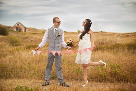 Happy bride and groom holding a garland with flags with the words  Just married  pose in the park on a background of yellow grass