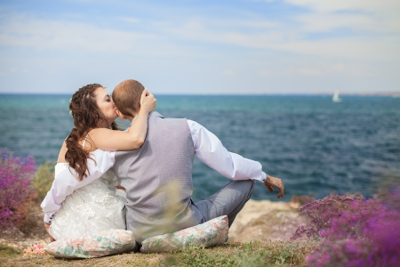 The bride and groom are sitting back watching the sea  Enjoy a moment of happiness and love in their wedding day  Stock Photo - 16569219