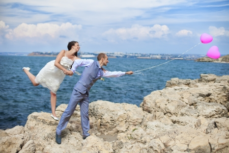 Happy bride and groom posing with balloons on a cliff on the background of the sea in their wedding day  Фото со стока