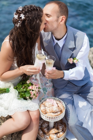 beautiful young couple in love bride and groom celebrating their wedding day on the cliffs by the sea with champagne and croissants  Series  Stock Photo - 16519573