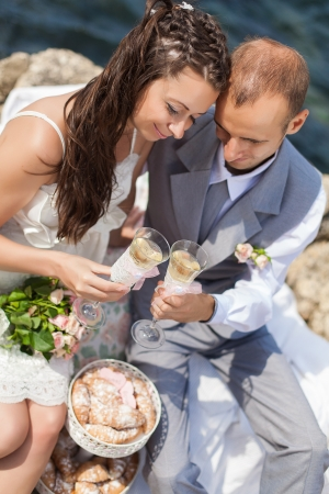 beautiful young couple in love bride and groom celebrating their wedding day on the cliffs by the sea with champagne and croissants  Series Stock Photo - 16519572