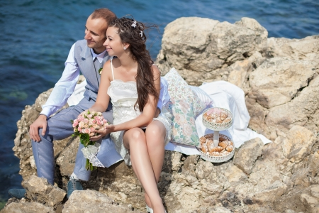 Happy pregnant bride and groom holding wedding bouquet posing against the sea  The groom tenderly embraces the pregnant belly of his wife  Stock Photo - 16501111