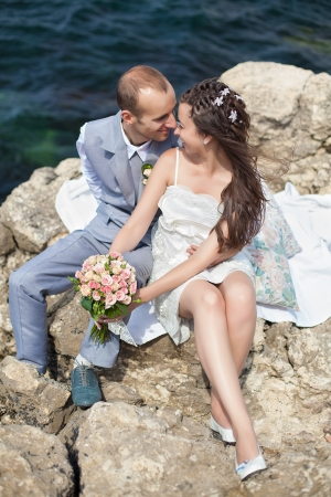 Happy pregnant bride and groom holding wedding bouquet posing against the sea  The groom tenderly embraces the pregnant belly of his wife  photo