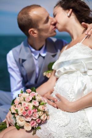 Happy pregnant bride and groom holding wedding bouquet posing against the sea  The groom tenderly embraces the pregnant belly of his wife Stock Photo - 16501061