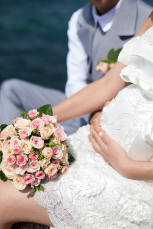 Happy pregnant bride and groom holding wedding bouquet posing against the sea  The groom tenderly embraces the pregnant belly of his wife Stock Photo - 16501063