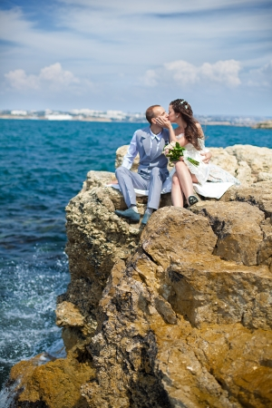 Happy pregnant bride and groom holding wedding bouquet posing against the sea  The groom tenderly embraces the pregnant belly of his wife Stock Photo - 16501112