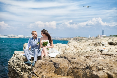Happy pregnant bride and groom holding wedding bouquet posing against the sea  The groom tenderly embraces the pregnant belly of his wife Stock Photo - 16501110