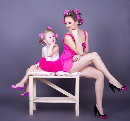A beautiful young mother with her daughter in the form of cheerful housewives  Studio shot on a gray background  Series photo