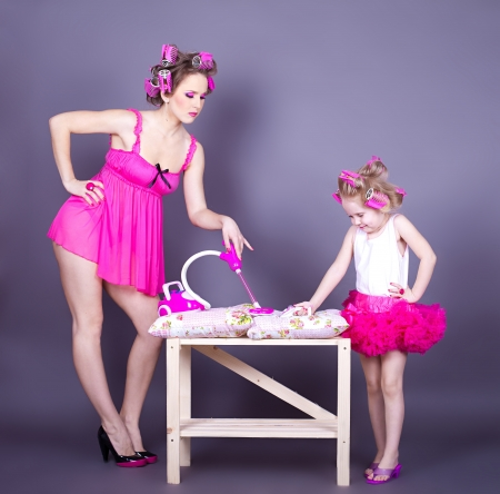 A beautiful young mother with her daughter in the form of cheerful housewives  Studio shot on a gray background  Series