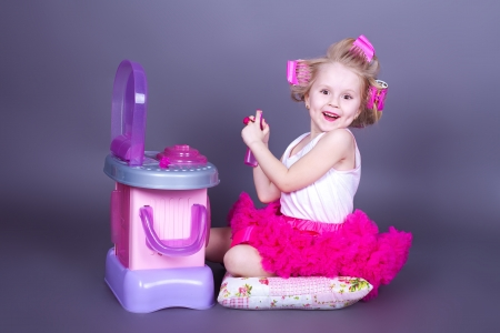 Funny little child does a make-up near the mirror  Stock Photo