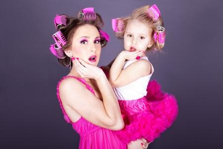 gente loca: Una madre hermosa joven con su hija en la forma de las amas de casa alegre Estudio dispar� sobre un fondo gris Series