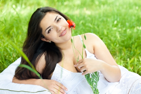 portrait of beautiful young woman laying on a green grass with flower in a park photo