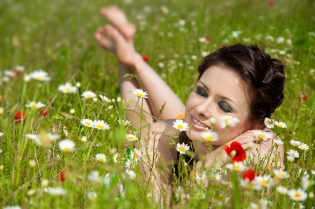 Young brunette girl smiling in the field of chamomile photo