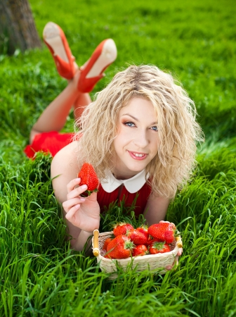 A beautiful young woman, a blonde with a basket of strawberries  Spring, bright green grass  A series of photos in my portfolio photo