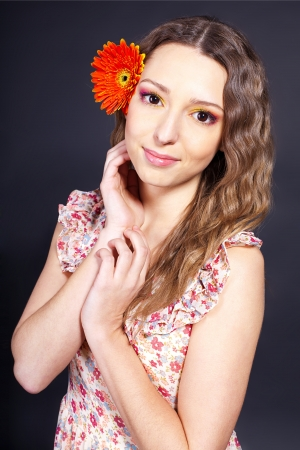 Beautiful young girl with a flower in her hair, Spring  Studio shot  Stock Photo - 16501749